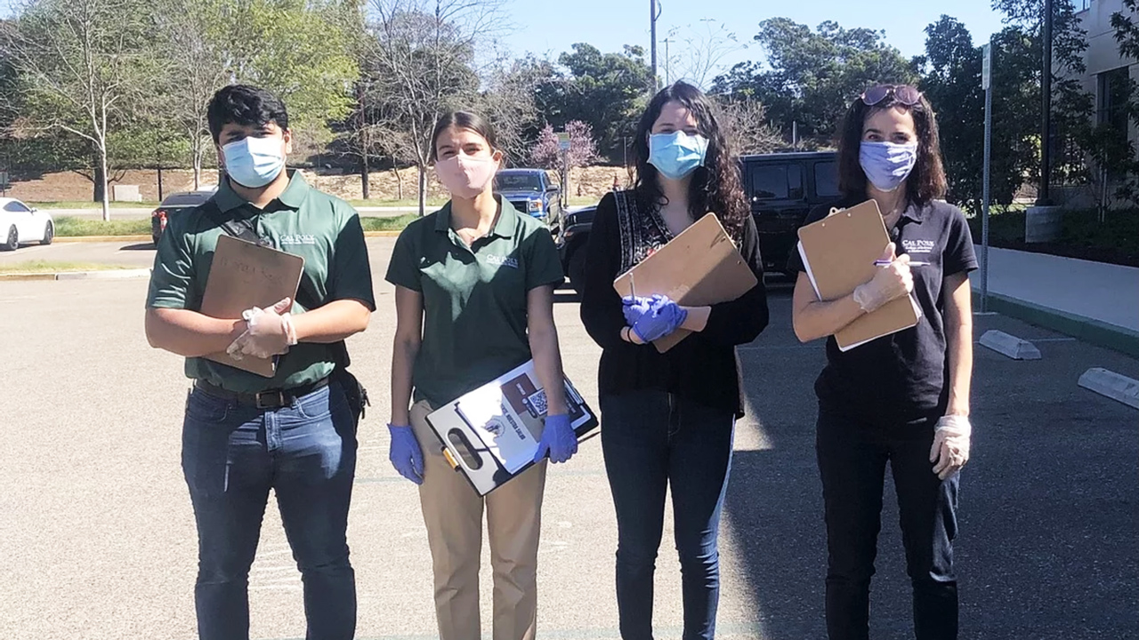 Four student researchers stand in masks holding clipboards