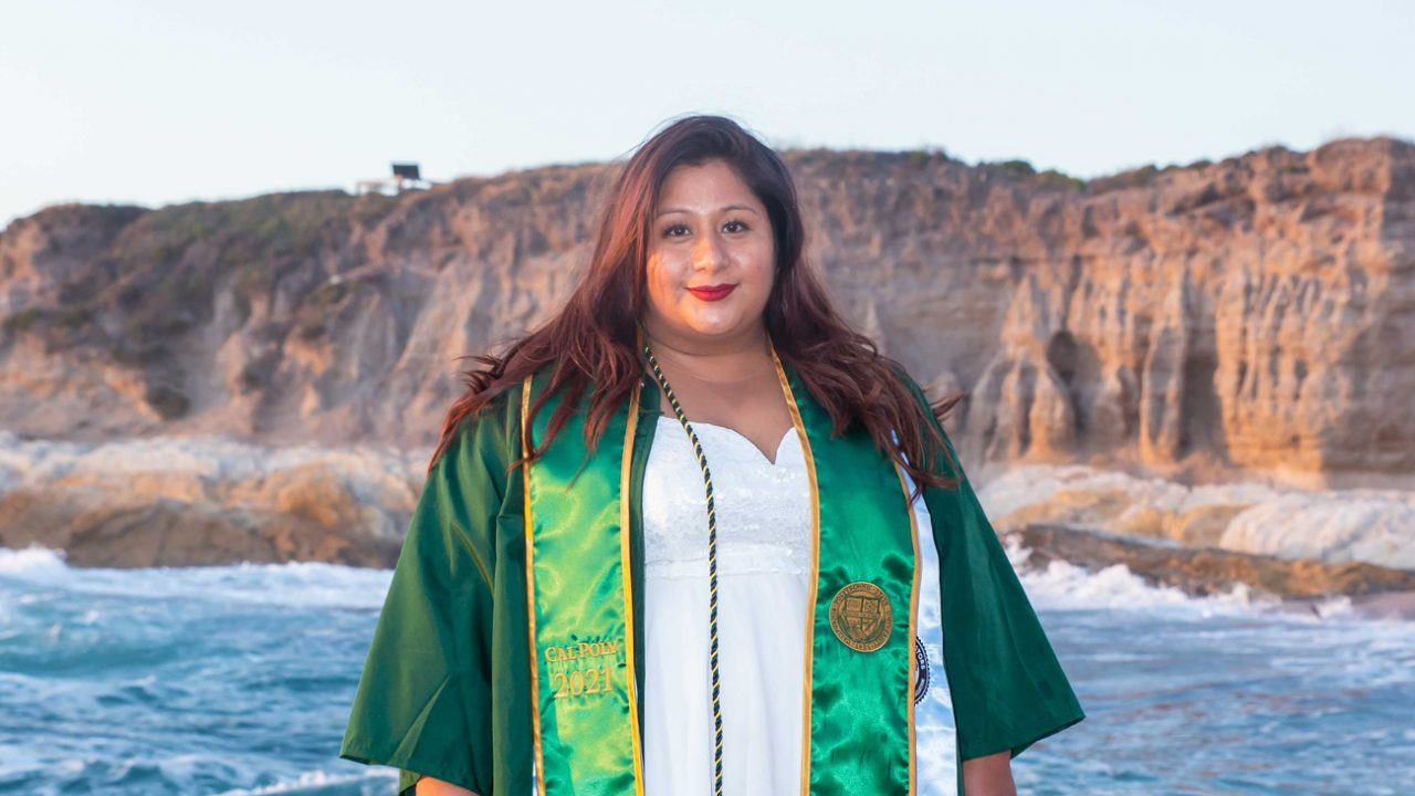 Francisca Camarillo stands in a green graduation gown and stole in front of the ocean