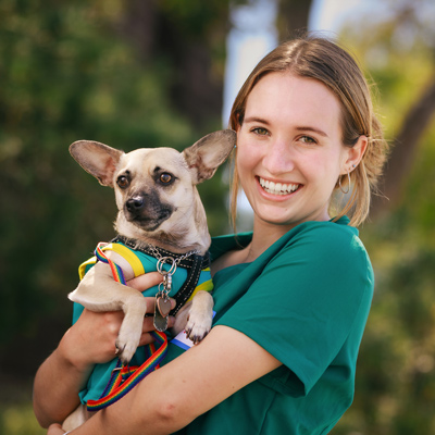 Lena Hoover wears green scrubs while smiling and holding a chihuahua named Milo