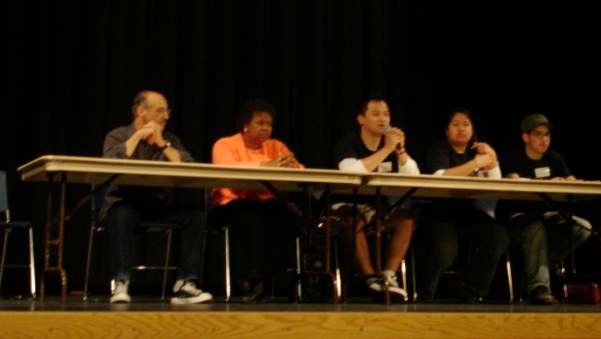 Five panelists sit behind a table with a microphone at the first PolyCultural Weekend event