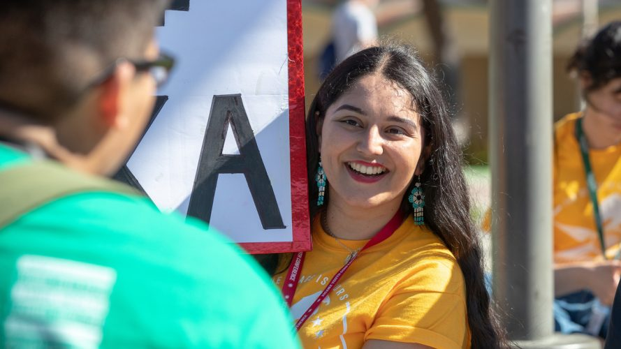 A student smiles while holding a MEXA club banner