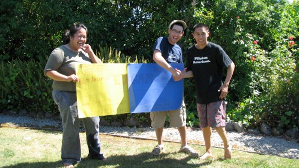 Janina Umali and Jonathan Reimers hold a yellow and blue banner while shaking hands with their mentor, Edgar Diaz