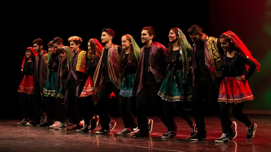 Students in embroidered clothing embrace on stage at PolyCultural Weekend