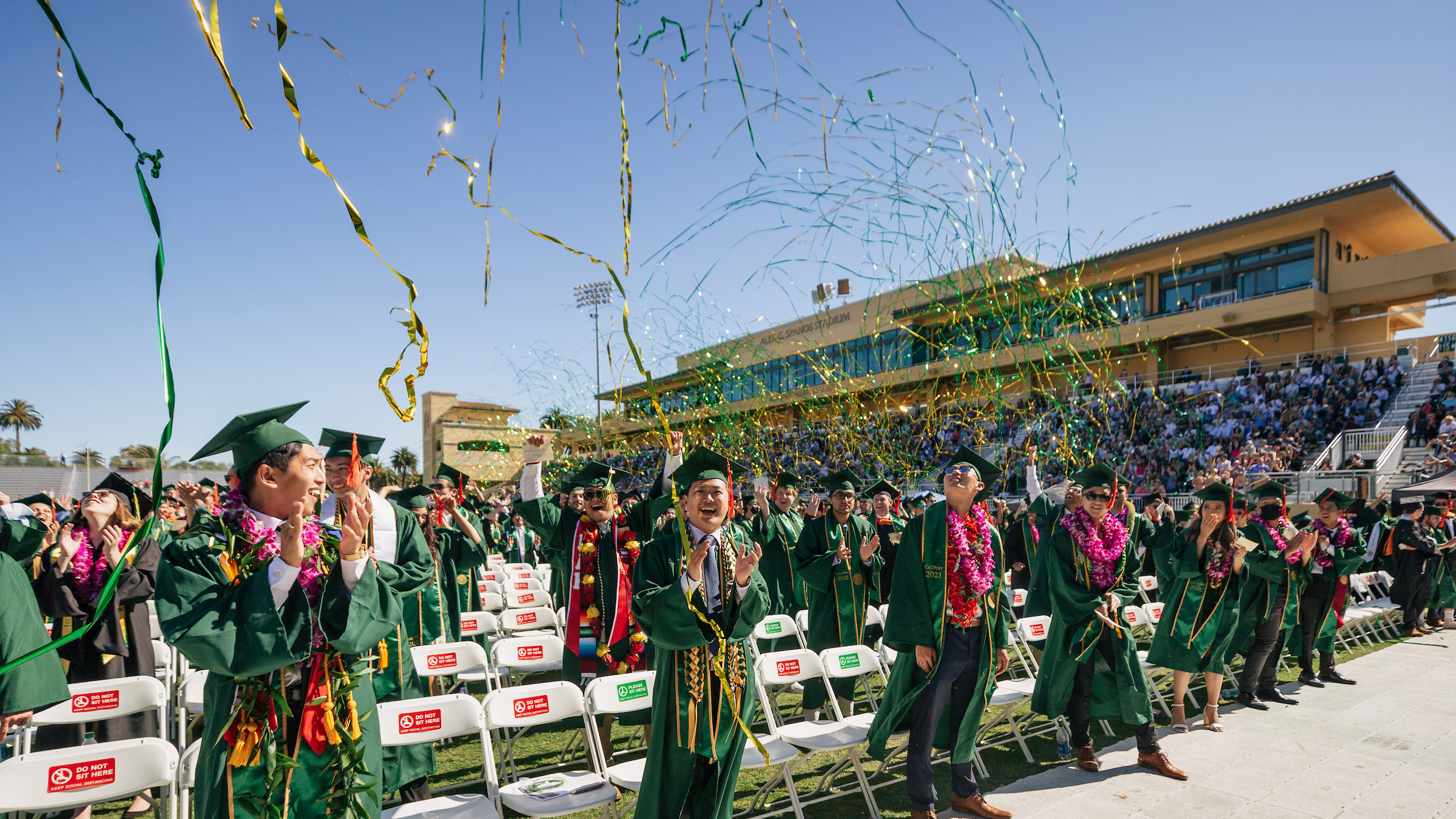 Graduates in green robes, spaced two seats apart, stand and cheer in Spanos Stadium as green and gold streamers fly through the air.