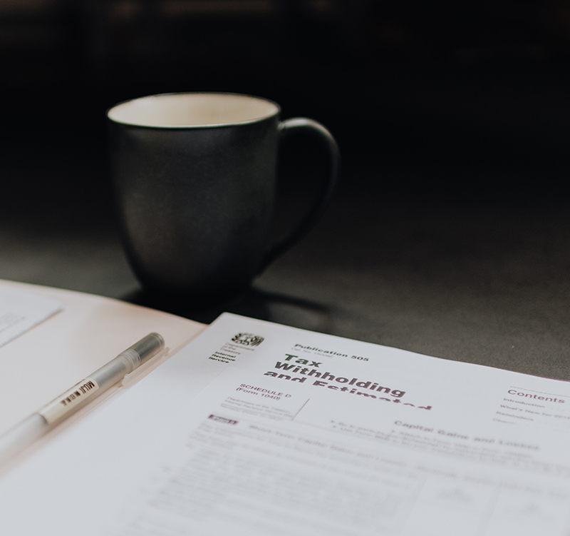 A stack of tax forms lies on a table top next to a black coffee cup and a pen