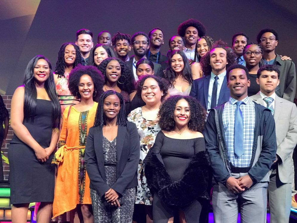 A group photo of the members of the Cal Poly chapter of the National Society of Black Engineers, in formal wear in front of a purple backgound