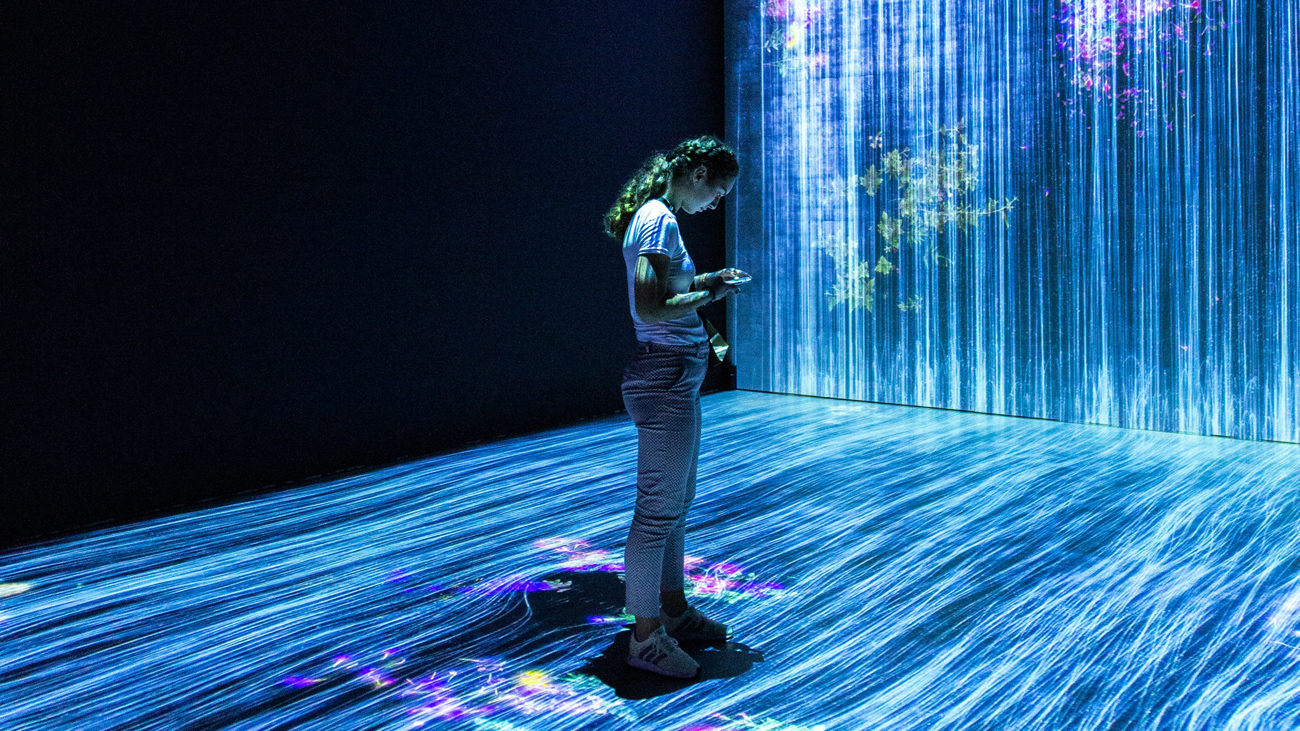 A person looking at a phone stands within an art installation with lights and blue graphics